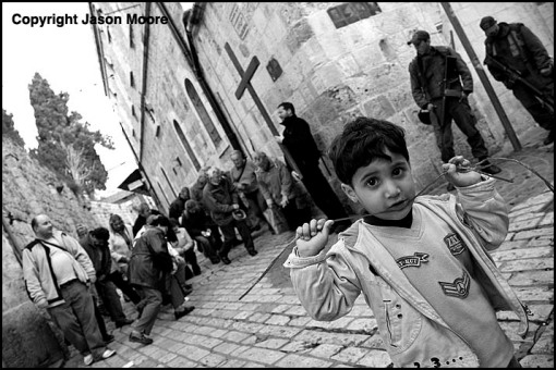 Christian pilgrims praying on the Via Dolorosa near a Palestinian child and Israeli police in the Old City of Jerusalem. The Via Dolorosa, also known as the Path of Sorrow, is the route taken by Jesus Christ through Jerusalem to his crucifixion.